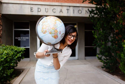 student holding a world globe in front of college of education buiidling