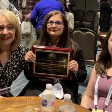 Group photo of Camelia Shaheed, Toni Saia and Zeynep Yilmaz holding award