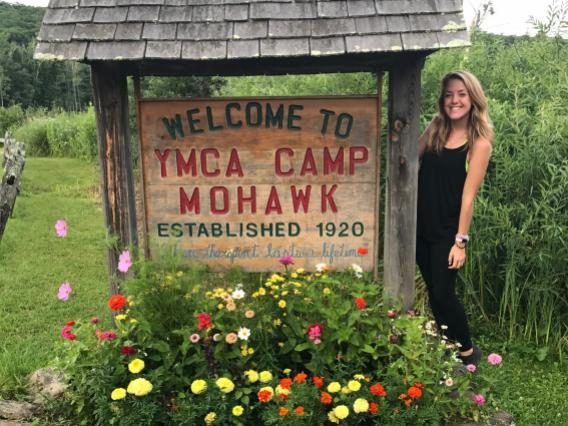 Alison posing in front of YMCA Camp Mohawk sign