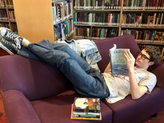 young man laying on a couch reading a book