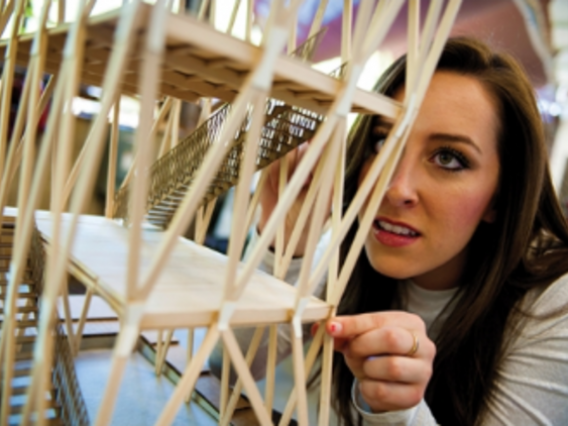 woman looking closely at a staircase model