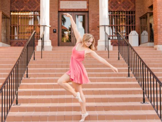 Nicole in a dance pose on steps leading up to a building