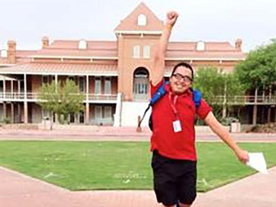 Student jumping up with a fist pump in front of old main