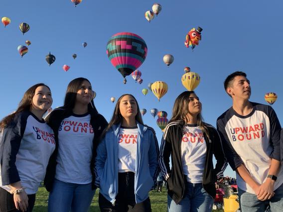students looking up at hot air balloons