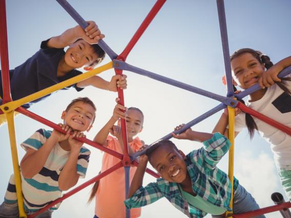 several kids looking down through playground structure