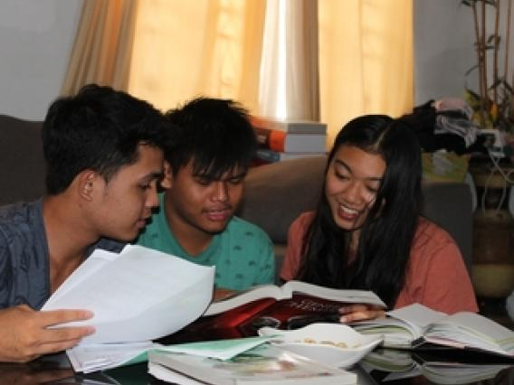 three students gathered around a table looking at a book
