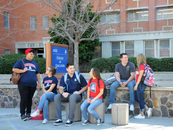 group of students sitting in front of college of education buidling