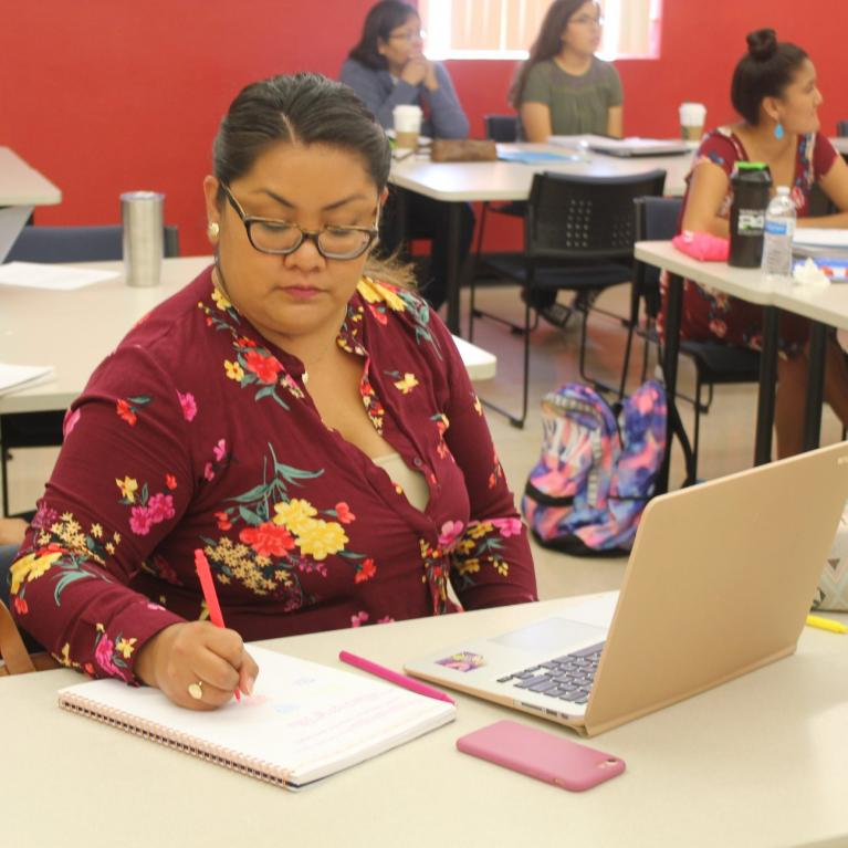ITEP student taking notes during lesson with Dr. Norma Gonzalez