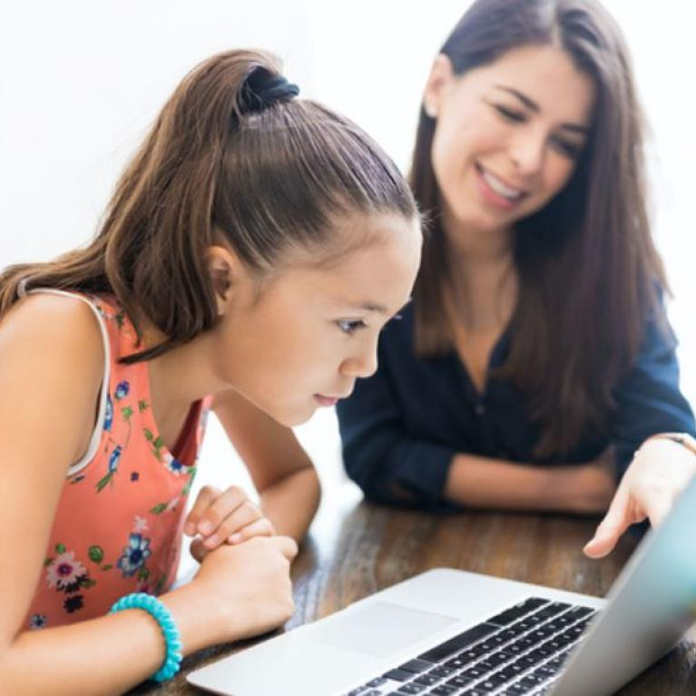 Young woman and child at table looking at laptop screen