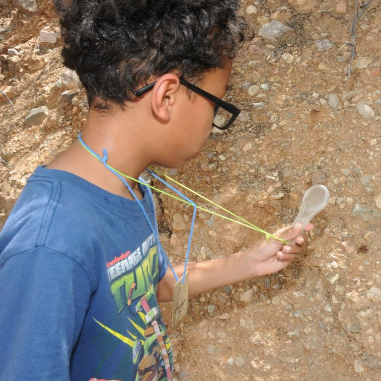 young boy inspecting dirt
