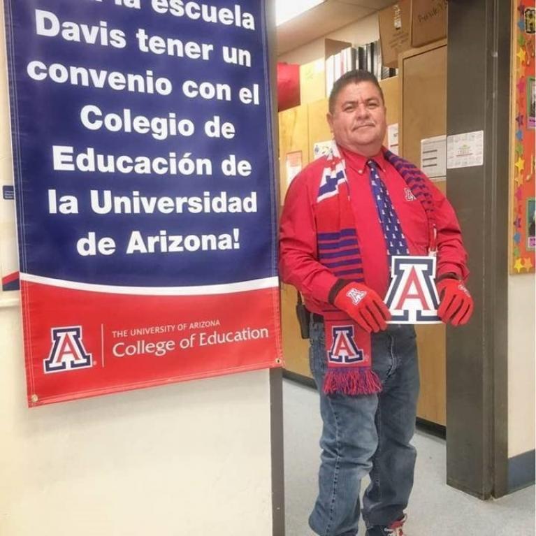Jose Olivas in UA gear standing next to spanish language banner
