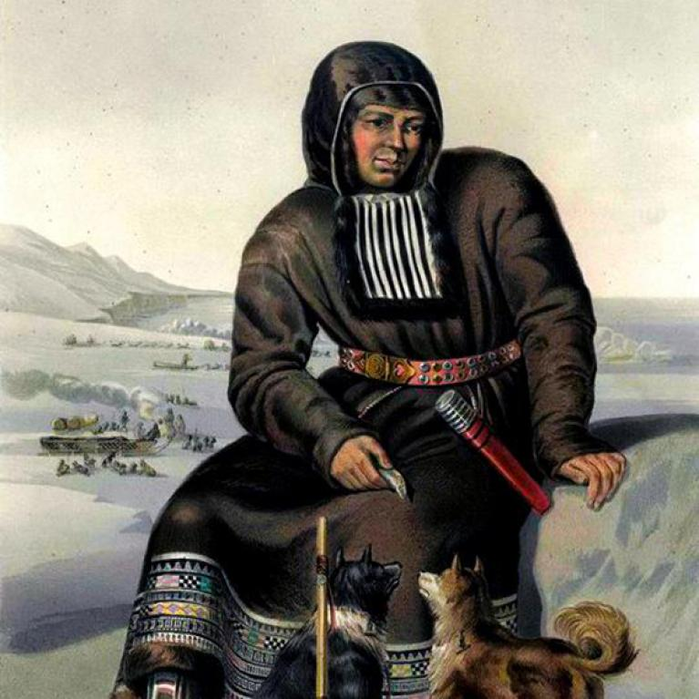 itlemen sitting on a rock with two dogs at his feet