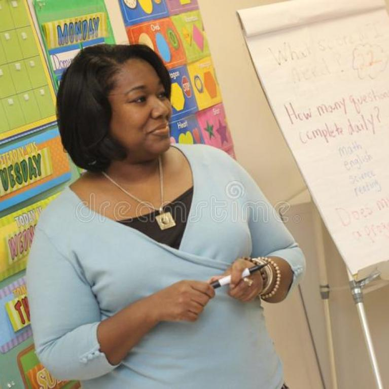 teacher standing in front of flip board