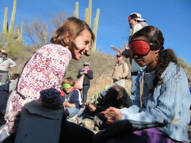 group of adults and students in desert setting