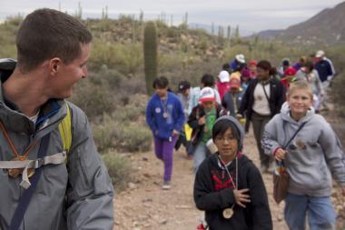 several children following a guide on a desert trail