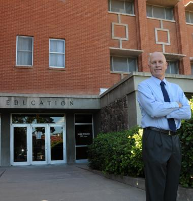 Dean Johnson posing in front of College of Education