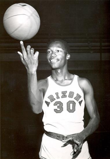 Ernie McCray in uniform spinning a basketball on his finger